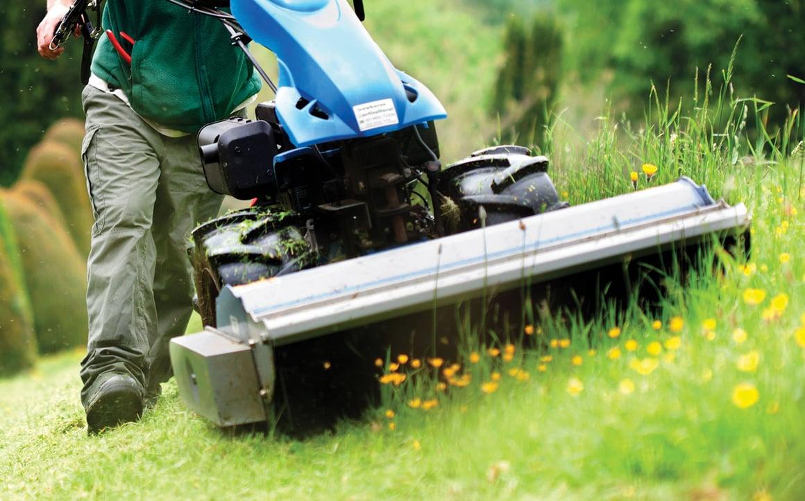 Man pushing equipment through grass