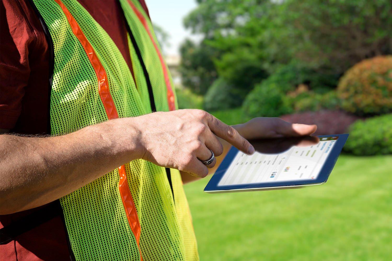 Man in utility vest holding tablet